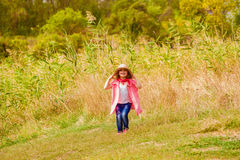 Little girl in jeans and a shirt near a river Royalty Free Stock Images