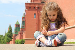 Little girl in jeans sits near old brick wall. Little girl in jeans sits on the asphalt near old brick wall and towers and tying shoelaces stock photography