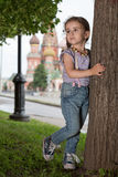 Little girl in jeans standing next to a tree. Little girl in jeans with suspenders standing next to a tree stock image
