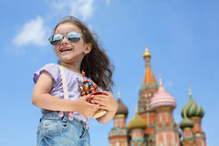 Little girl in jeans with suspenders with a miniature cathedral. Smiling little girl in sunglasses and jeans with suspenders with a miniature cathedral royalty free stock image