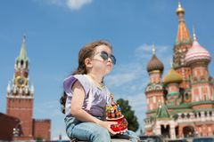 Little girl in jeans with suspenders with a miniature cathedral. Little girl in sunglasses and jeans with suspenders with a miniature cathedral sitting near the stock image