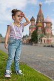 Little girl in jeans with suspenders near the Saint Basils Cathedral. Look into the distance stock photos
