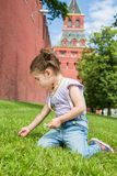 Little girl in jeans with suspenders picking flowers. In hand near old brick wall and tower royalty free stock photo