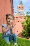 Little girl in jeans with suspenders sitting on the grass. Near old brick wall and tower stock photos