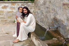 Little girl and Jesus at the water well. Biblical scene when Jesus says, let the little children come to me, blessing a little girl. Historical reenactment at an Royalty Free Stock Image