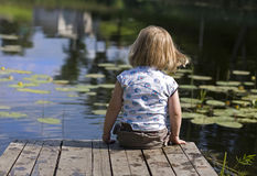 Little girl on jetty. Little girl sits on wooden jetty and looks at water Royalty Free Stock Photography