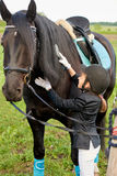 Little girl jockey attend and brushing her horse stock images