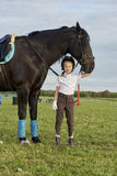 Little girl jockey communicating with her black horse in professional outfit Royalty Free Stock Photos