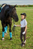 Little girl jockey communicating with her black horse in professional outfit. Pretty little girl jockey communicating with her black horse in professional outfit stock photo