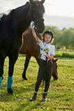 Little girl jockey communicating with her black horse in professional outfit Stock Photo
