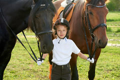 Little girl jockey communicating with her horses in professional outfit Royalty Free Stock Images