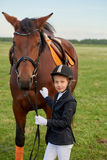 Little girl jockey lead horse by its reins across country in professional outfit Stock Photos