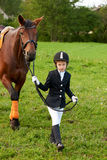 Little girl jockey lead horse by its reins across country in professional outfit Royalty Free Stock Photo