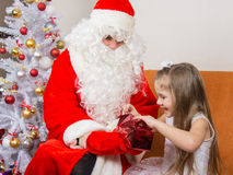 Little girl joyfully opens gift that keeps grandfather frost Royalty Free Stock Photo