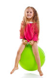 Little girl jump on a big green ball Royalty Free Stock Image