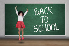 Little girl jump in the classroom stock photography
