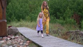 Little girl jump off big stone and walk with her mother through wooden path stock video footage