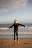 Little girl jumping. A cute little girl jumps for joy on the beach at sunset Stock Photos