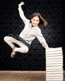 Little girl jumping. With a stack of books Stock Image