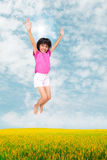 Little girl jumping against beautiful sky Stock Photos