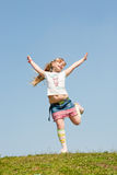 Little girl jumping against beautiful sky Royalty Free Stock Photos