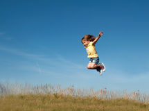 A little girl jumping against the blue sky background Stock Photos