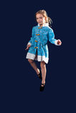 Little girl jumping in the air in the blue dress. Stock Images