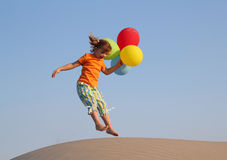 Little girl jumping with balloons. Happy little girl jumping with balloons Royalty Free Stock Images