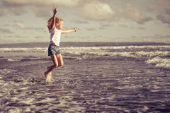 Little girl  jumping on the beach at blue sea shore Stock Photography
