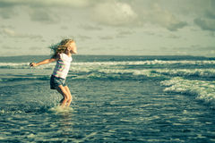 Little girl  jumping on the beach at blue sea shore Stock Images