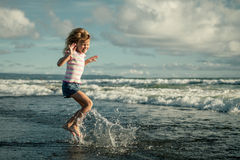 Little girl jumping on the beach Royalty Free Stock Photos