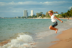 Little girl jumping on the beach at the day time Royalty Free Stock Image