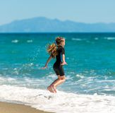 Little girl jumping on the beach Stock Photos