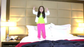 Little girl jumping in bed stock video