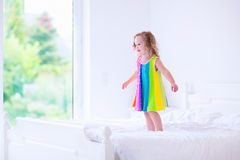 Little girl jumping on a bed. Children jump on a bed. Cute little girl jumping and dancing in a sunny white bedroom. Kids room with garden view window. Toddler Stock Image