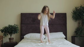 Little girl jumping on the bed at home stock footage