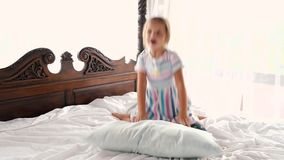 Little girl jumping on the bed at home stock video footage