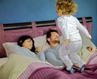 Little girl jumping on bed while parents are sleeping royalty free stock photography