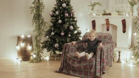 Little girl jumping in a chair for the new year on the background of Christmas decorations stock video footage