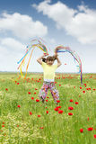 Little girl jumping and with colorful ribbons Stock Images