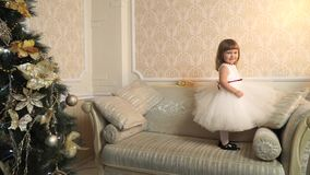 Little girl jumping on the couch, and flaunts a beautiful in her dress stock video footage