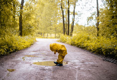 Little girl jumping fun in a dirty puddle Stock Image