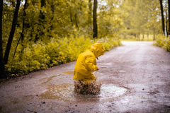 Little girl jumping fun in a dirty puddle Stock Images