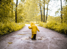 Little girl jumping fun in a dirty puddle Royalty Free Stock Images