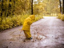 Little girl jumping fun in a dirty puddle Royalty Free Stock Image