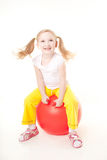 Little girl jumping on gymnastic ball. Cute sly little girl doing gymnastic exercise with ball Stock Images