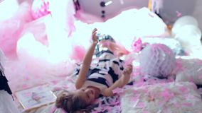 Little girl jumping and having fun celebrating birthday. Portrait of a child throws up multi-colored tinsel and confetti. Positive emotions. Happy excited stock footage