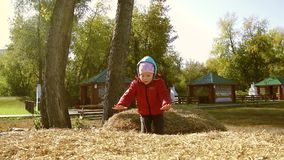 Little girl jumping in haystack stock video