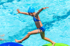Little girl jumping on inflatable water mattress in pool. Stock Image