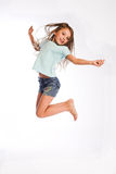 Little girl jumping of joy. Little smiling girl jumping of joy on white background Royalty Free Stock Photography